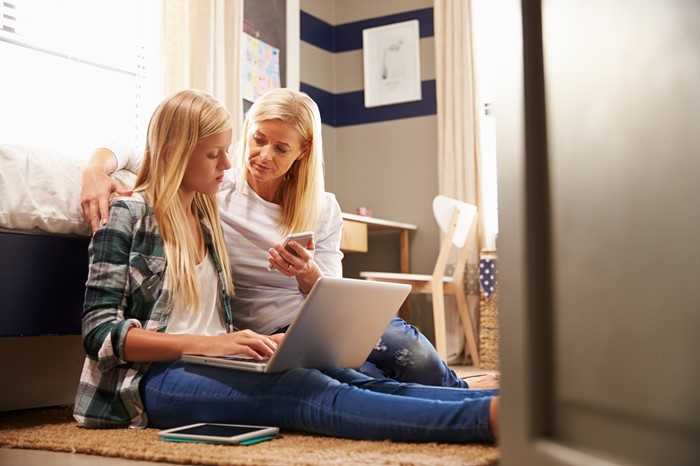 Woman sitting on laptop with daughter